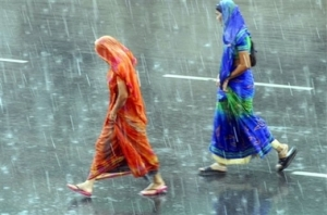 Indian women walk in the rain during a sudden downpour in Hyderabad, India, Wednesday, June 13, 2007. Severe monsoon weather which devastated Bangladesh extended its grip over South Asia on Wednesday, killing a dozen people and disrupting transport in eastern India, according to a news report. (AP Photo/Mahesh Kumar A)